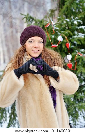Cheerful Charming Young Woman In A Fur Coat Makes Heart Fingers