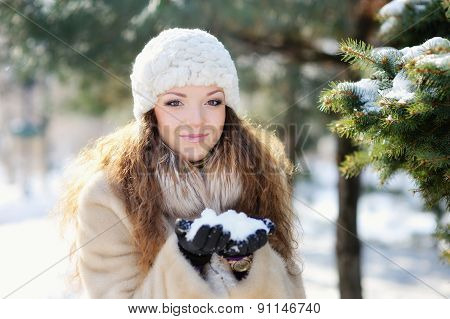 Young Woman In Hat And Mittens Laughing Playing With Snow Outdoors.