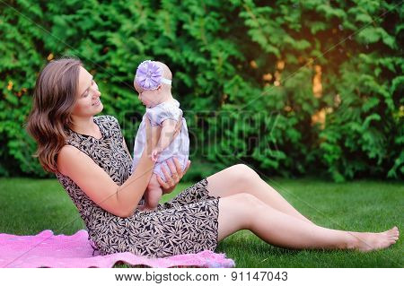 Mum Holds On Hands Of A Little Daughter Outdoors In Park