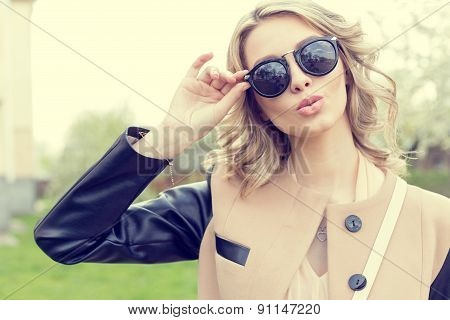 Beautiful young sexy girl in sun glasses walking on a bright sunny summer day on city streets