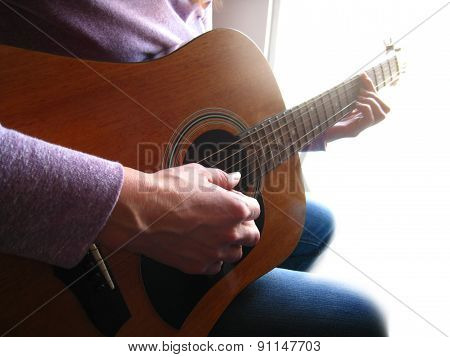 Close-up of Woman Playing Guitar in the Light