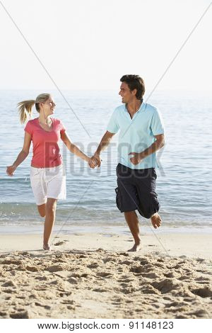 Young Couple Running Along Beach On Holiday