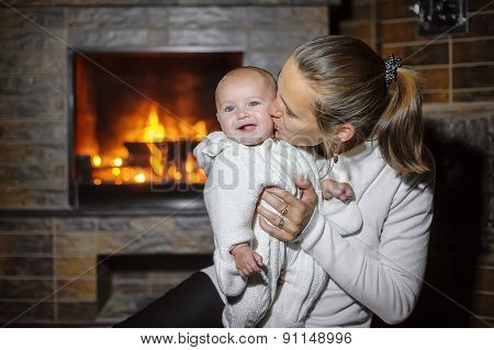 Mom Kissing Baby By The Fireplace At Home