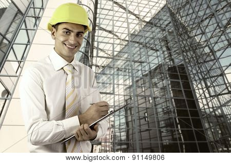 Young architect wearing a protective helmet standing on the building outdoor background