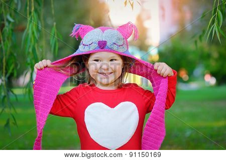 Beautiful Laughing Little Toddler Girl In A Red Coat And Colorful Knitted Hat And Scarf Playing With