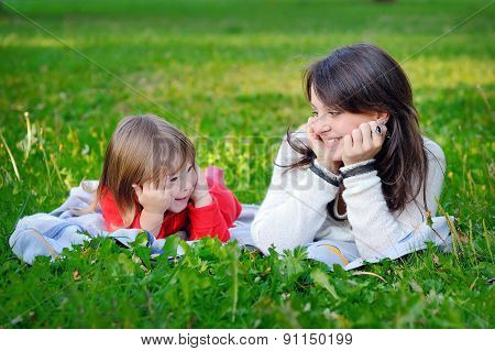 Portrait Of Smiling Beautiful Young Woman And Her Little Daughter Sitting On Grass, Against Green Of