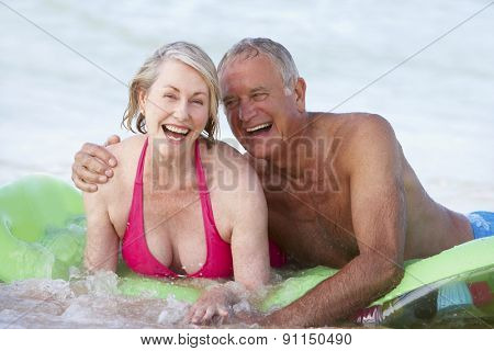 Senior Couple Having Fun In Sea On Airbed