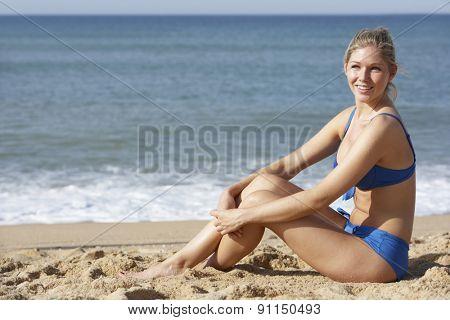 Young Woman Wearing Bikini Sitting On Beach