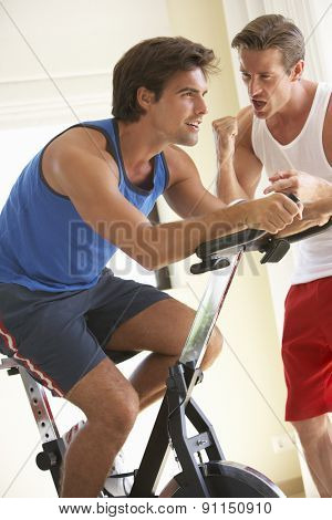 Young Man On Exercise Bike With Trainer