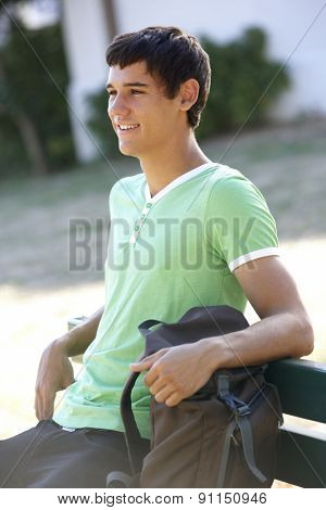 Male College Student Sitting On Bench With Backpack