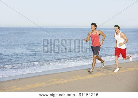 Two Young Men Jogging Along Beach