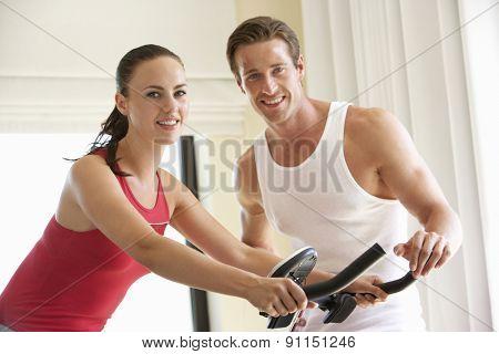 Young Couple On Exercise Bike