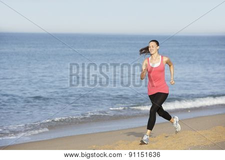 Young Woman Jogging Along Beach