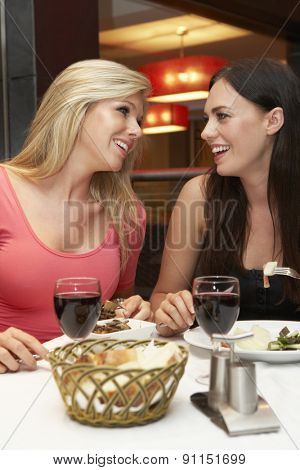 Two Young Women Enjoying Meal In Restaurant