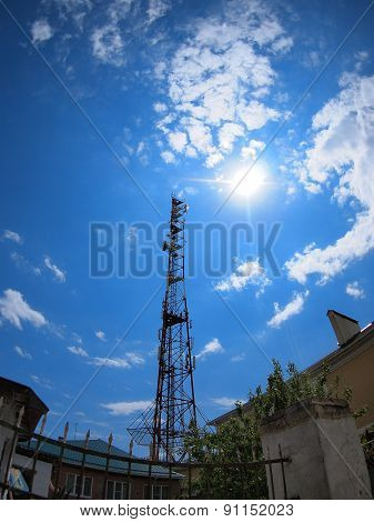 Tower Of Cellular Communication Against The Blue Sky And Bright Sun