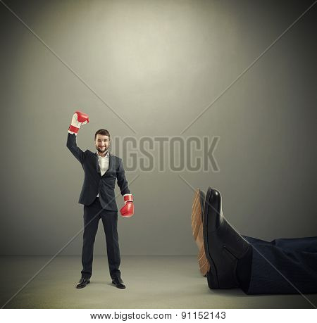 happy winner businessman in red boxing gloves standing near big lying mans legs over dark grey background