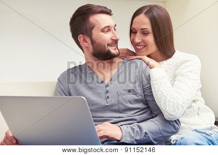 indoor photo of smiley couple sitting on sofa, man holding laptop and looking at woman