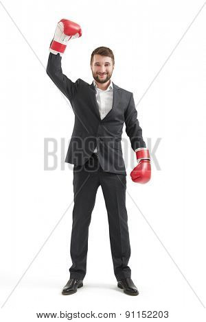 full length portrait of smiley businessman in formal wear and red boxing gloves raising up one hand and looking at camera. isolated on white background