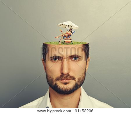small attractive woman in bikini lying on beach chair and holding cocktail on the green meadow in mans head of big displeased man. photo over grey background