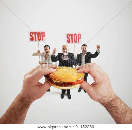 concept of harmful fast foods. small people screaming and holding placard with stop sign, big hands holding fat burger and ready to eat it