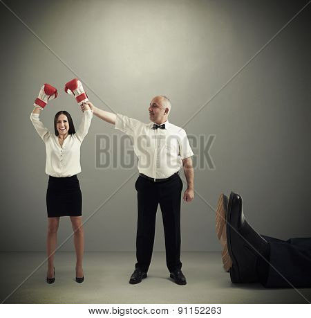 smiley referee holding winner businesswoman in boxer gloves and looking at her, near lying big legs of knocked out businessman over dark grey background