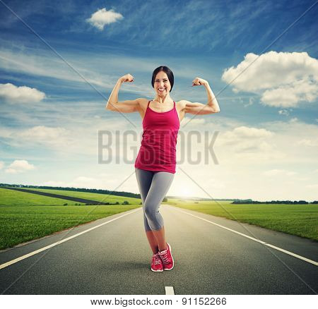 outdoor photo of smiley woman showing her biceps and looking at camera