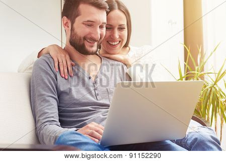 indoor photo of smiley young couple sitting on sofa and using laptop