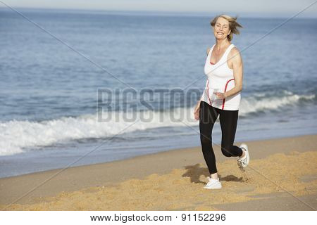 Senior Woman Jogging Along Beach