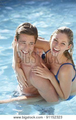 Young Couple Relaxing In Swimming Pool Together
