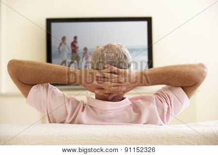 Senior Man Watching Widescreen TV At Home