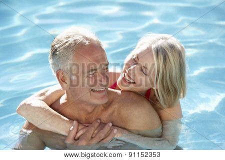 Senior Couple Relaxing In Swimming Pool Together