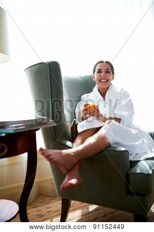 Woman Lounging In Chair With Legs Over Chair Arm.