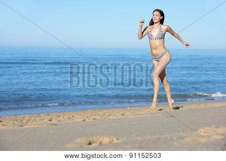 Young Woman Running Along Summer Beach