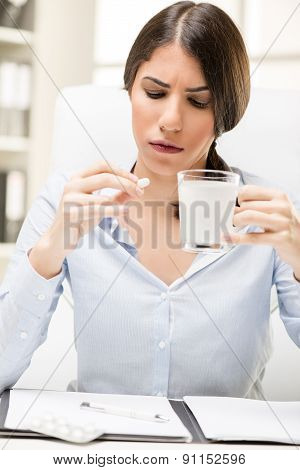 Young Woman Takes A Pill At Work