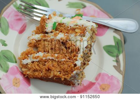 Thin slice of carrot cake on floral plate