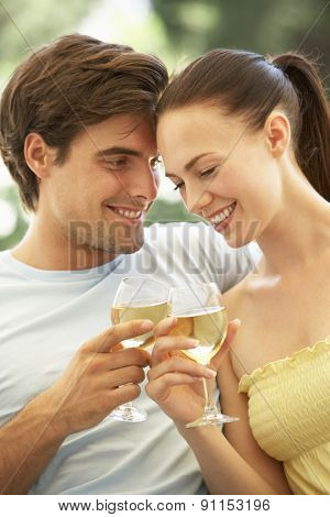 Portrait Of Young Couple Relaxing On Sofa Drinking Wine Together