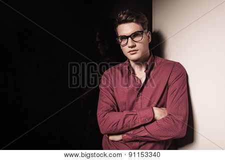 Casual young business man standing with his hands crossed while leaning on a grey wall.
