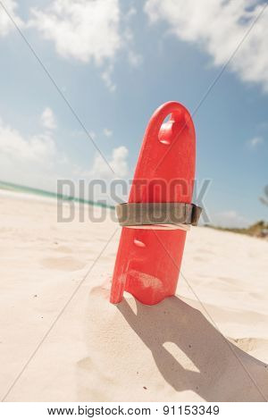 Picture of a red plastic life guard tube, on the beach.