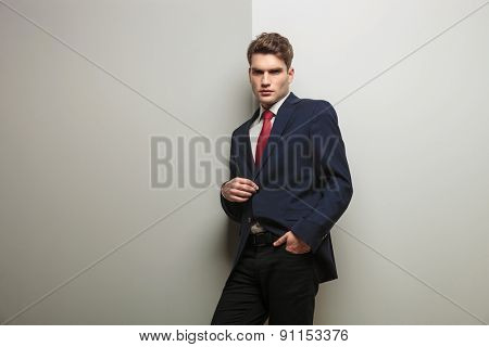 Side view of a young business man opening his jacket while leaning on a grey wall.