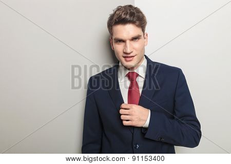 Smiling young business man looking at the camera while fixing his collar