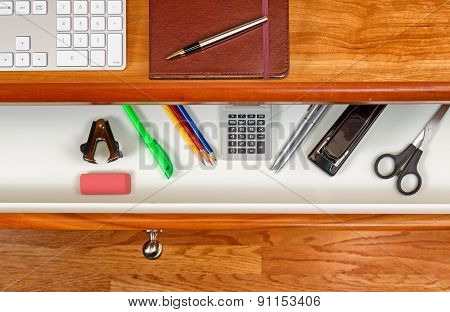Organized Desktop And Open Drawer With Wooden Floor Underneath