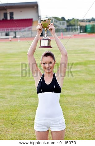 Cheerful Female Athlete Holding A Trophee