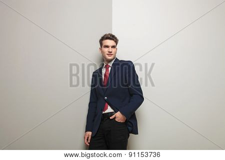 Young business man holding one hand in his pocket while leaning on a grey wall.