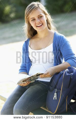 Female College Student Sitting On Bench With Backpack