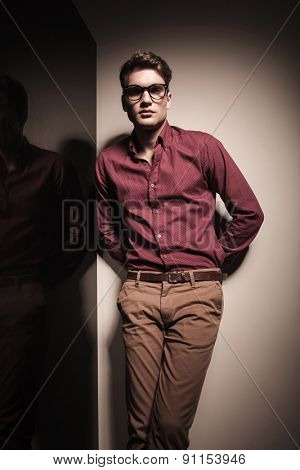 Young casual business man leaning on a  grey wall holding his hand behind.