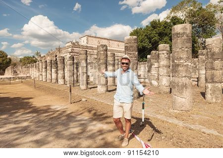 Happy man inviting you to visit the ruins in Chichen Itza, Mexico.