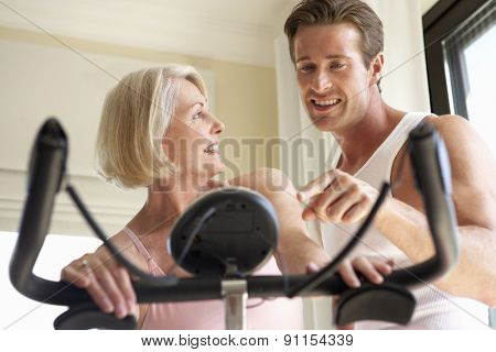Senior Woman On Exercise Bike With Trainer
