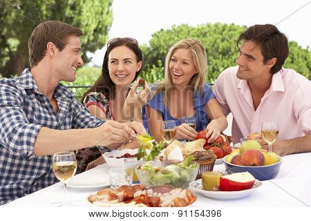Group Of Young Friends Enjoying Outdoor Meal Together