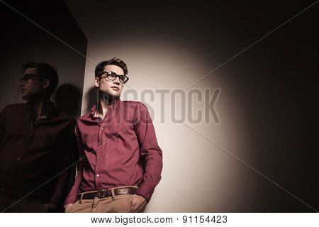 Down view of a young casual business man looking away while leaning on a wall with his hands in pockets.