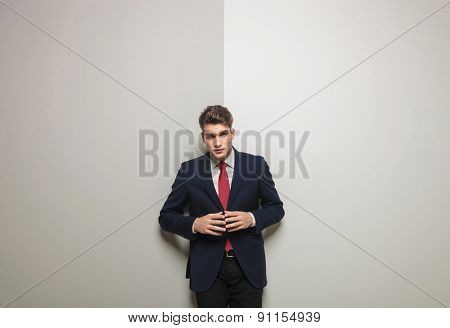 Attractive young business man holding his hand together trying to make a decision.